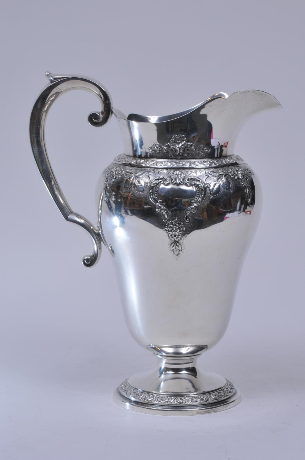 """Watson Company. Sterling silver large water pitcher. Shaped spout. Floral repousse and chased relief decoration. 11-1/2"""" high. Good condition. 31 ozt."""