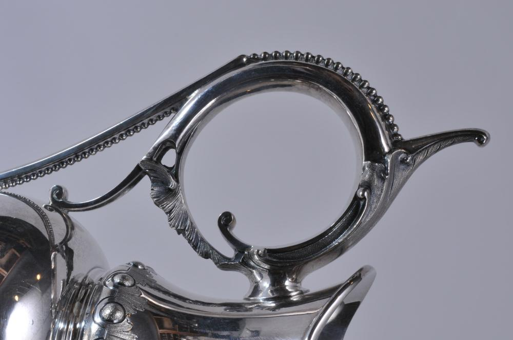 "Lot 64: W & H makers coin silver Victorian large ewer. Leaf and beaded decorated handle. Floral repousse cartouche decoration. Beaded and dart borders. Inscription on body. 13-3/4"" high. 37.5 ozt. Good condition."