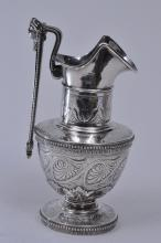 """Lot 67: Tiffany & Co. Makers. Sterling silver Victorian small handled ewer with figural head handle. Greek key and beaded borders. Relief and engraved leaf decoration. Heraldic crest near spout. 7-3/4"""" high. 13.5 ozt. Good condition."""