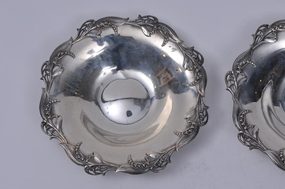 "Lot 72: Pair of Tiffany & Co. makers sterling silver round bowls. Raised floral bellflower pierced decorated rims. 7-3/4"" diameter. 12.9 ozt."