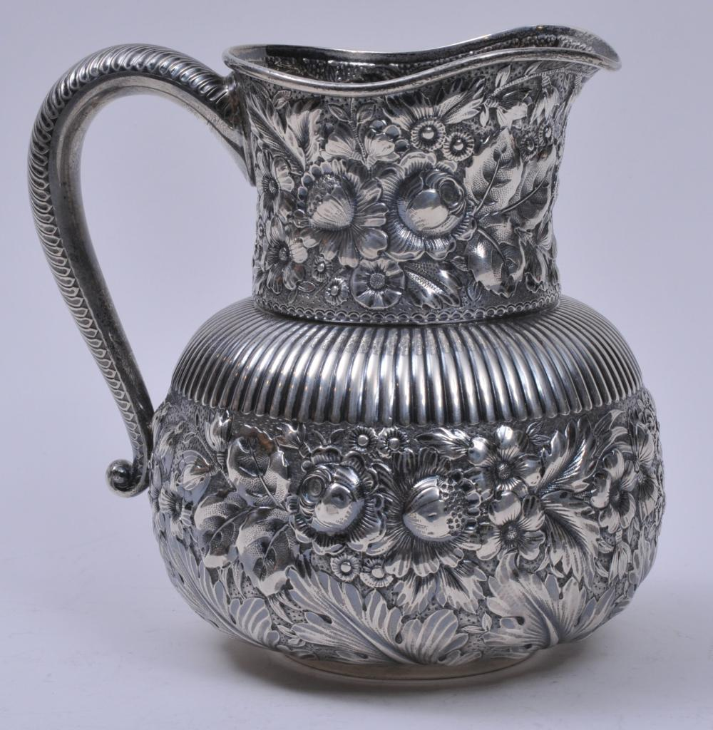 """Gorham sterling silver Victorian Aesthetic style floral repousse decorated pitcher with ribbed body. Leaf decorated handle. A couple of areas in repousse that might be slightly dented. 7-1/2"""" high.  20.1 ozt."""