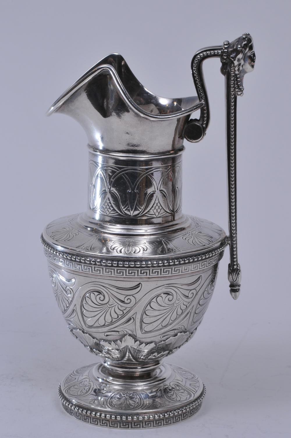 """Tiffany & Co. Makers. Sterling silver Victorian small handled ewer with figural head handle. Greek key and beaded borders. Relief and engraved leaf decoration. Heraldic crest near spout. 7-3/4"""" high. 13.5 ozt. Good condition."""