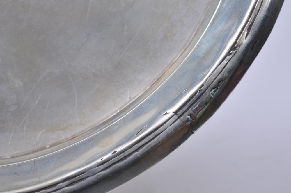 "Lot 75: 18th/19th century silver round footed tray. Circle and ball feet. Repairs to rim. Unmarked. Small dents. 7-1/2"" diameter. 7.7 ozt."