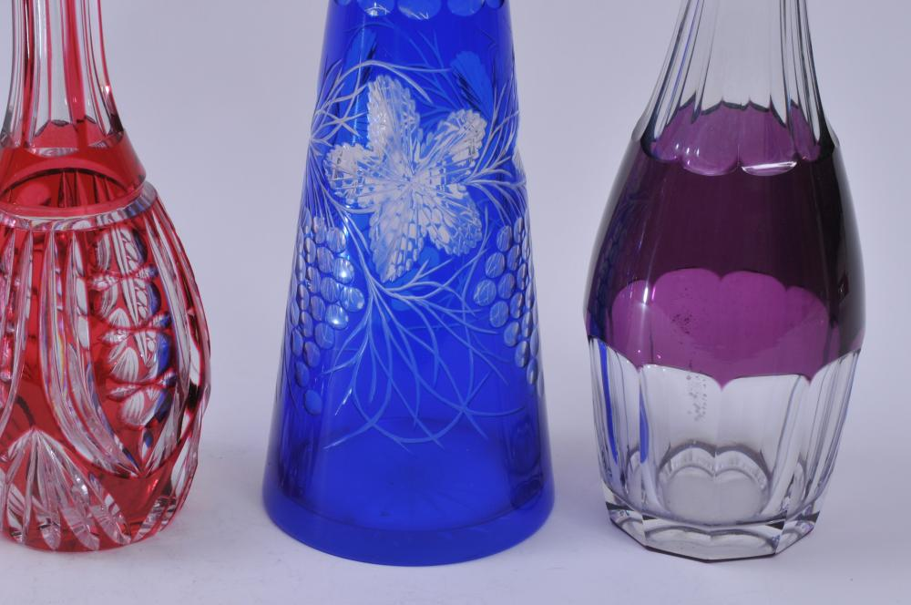 "Lot 77: Lot of five colored cut to clear glass decanters. Three- red cut to clear. One- blue cut to clear. One- purple cut to clear. Red decanters- 12-1/2"" to 13"" high. Blue decanter- 16"" high. Purple decanter- 16-1/2"" high."