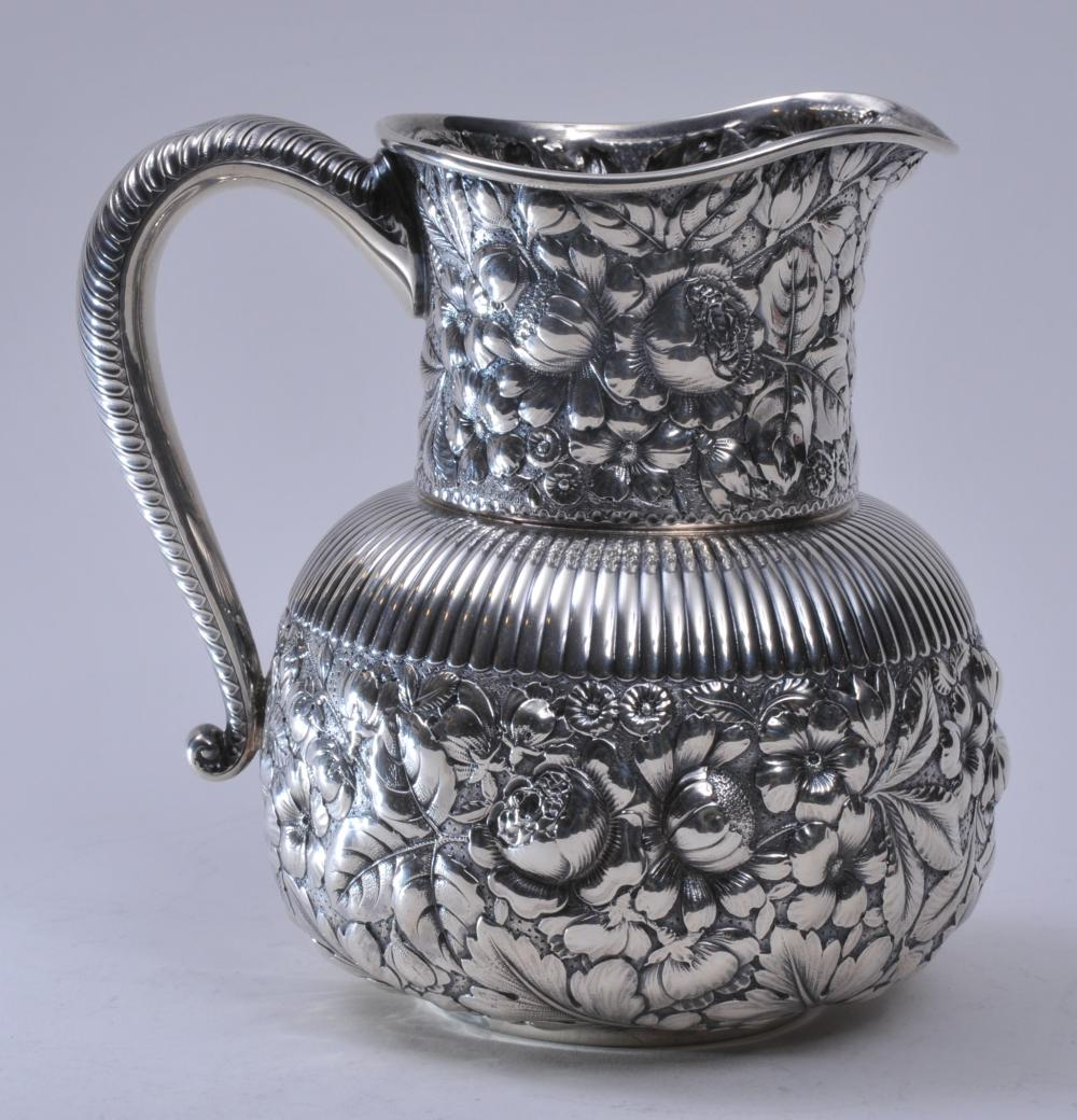 """Lot 76: Gorham sterling silver allover floral repousse pitcher with ribbed body and leaf handle decoration. Stippled ground. Pushed in area where body meets base. Can be accessed through top. 1/2"""" dent on handle. 7-1/2"""" high. Inscription on base 1889. 21.5 o"""