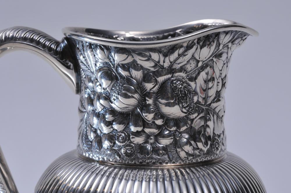 "Lot 76: Gorham sterling silver allover floral repousse pitcher with ribbed body and leaf handle decoration. Stippled ground. Pushed in area where body meets base. Can be accessed through top. 1/2"" dent on handle. 7-1/2"" high. Inscription on base 1889. 21.5 o"
