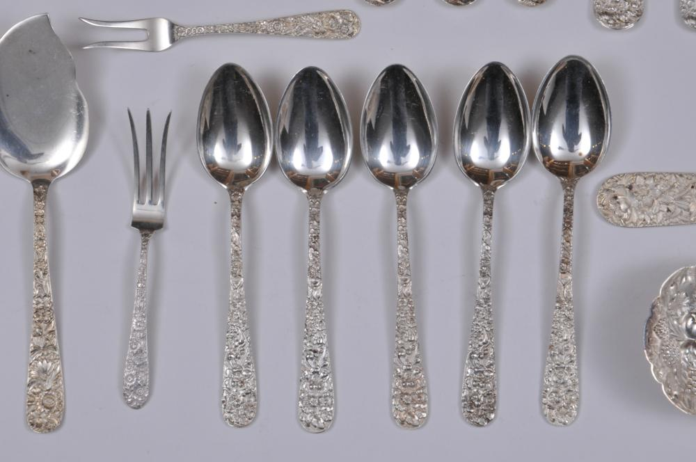 """Lot 81: Stieff floral repousse decorated sterling silver 29 piece partial flatware set. Includes: (3) forks- 7-1/4"""". (4) forks- 6-7/8"""". (5) salad forks- 6"""". (5) teaspoons- 5-7/8"""". (2) solid butter knives- 6"""". (4) knives- 8-3/4"""". (1) large berry spoon- 9"""". (1"""