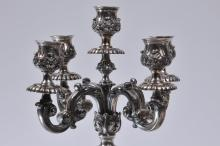 Lot 84: Pair of large heavy sterling silver five light ornate candlelabras. High relief cast leaf and scroll decoration. Ribbed candleholders and shafts. Engraved and stippled ground decoration. Shell and stepped pad feet. Marked on base rim above feet. Some