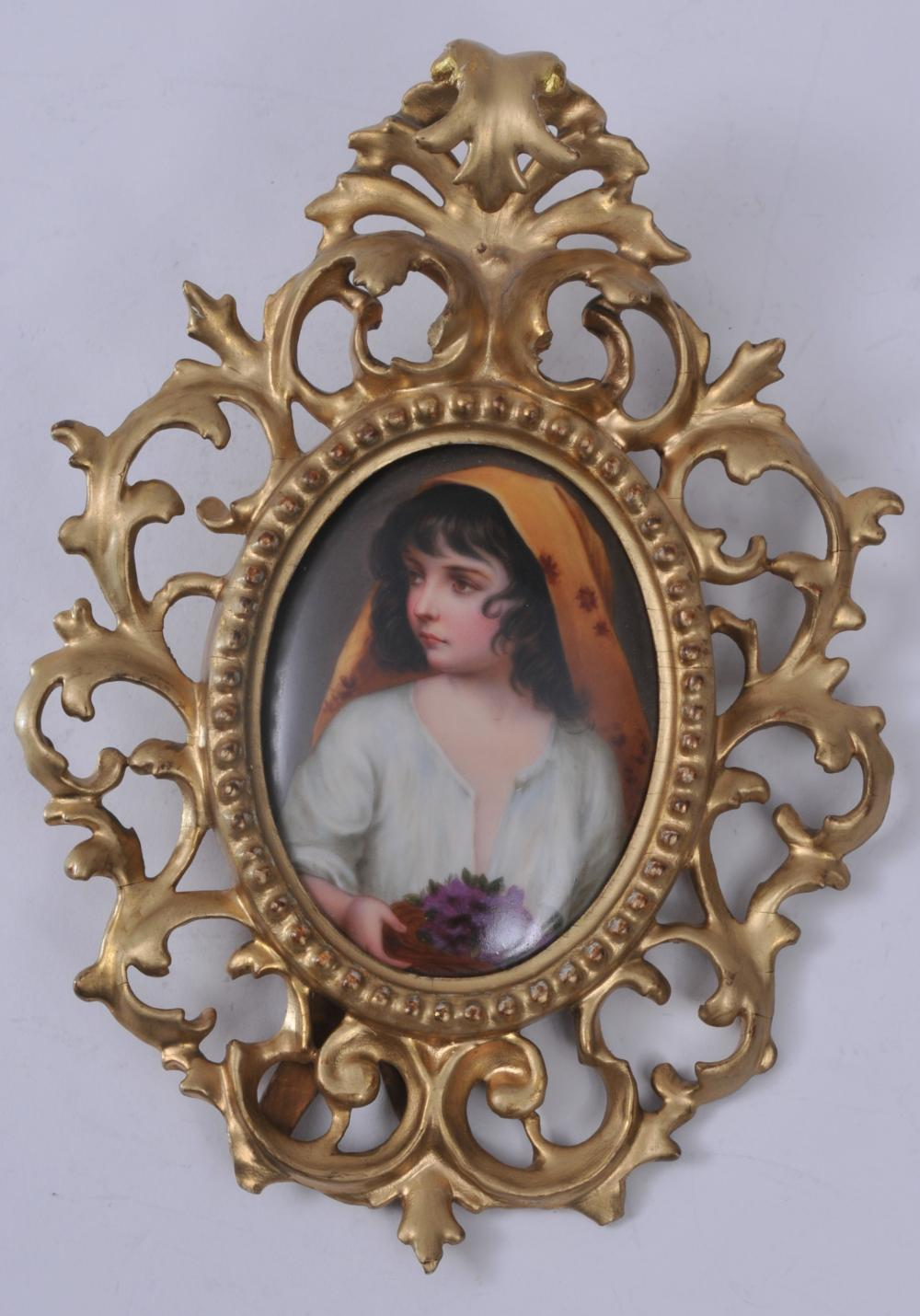 """19th century Continental painting on porcelain framed plaque. Oval hand painted scene of a young girl holding flowers. Gilt carved wood frame. Touch up to gilt on frame. 10-1/2"""" overall size. Plaque- 4-1/2""""  x 3-1/4""""."""
