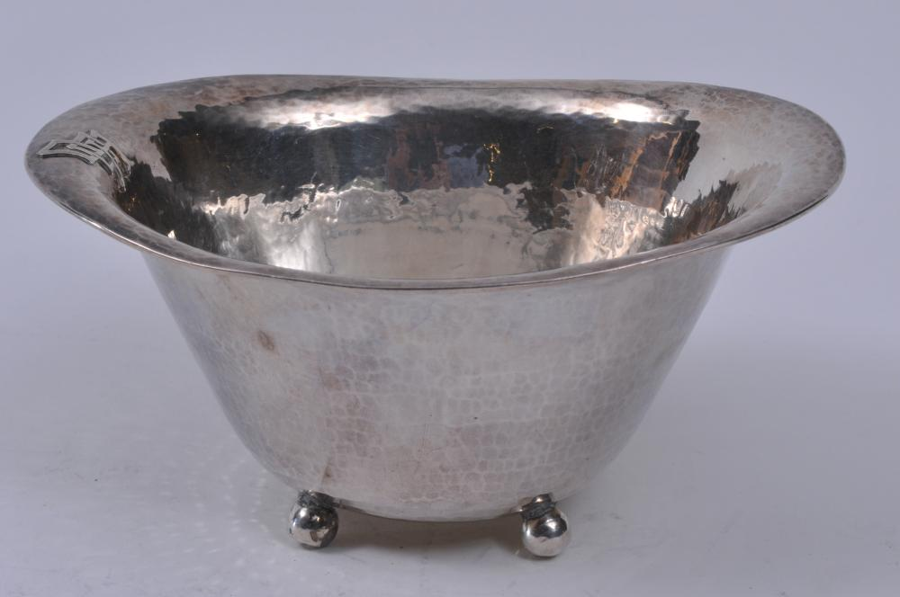 """Lebolt hand made Arts and Crafts oval ball footed bowl. Hand hammered surface. Applied Arts and Crafts monogram on top rim.  6-3/4"""" wide. 3"""" high. Light scratches. Small dent on bottom of one ball foot.  7 ozt."""