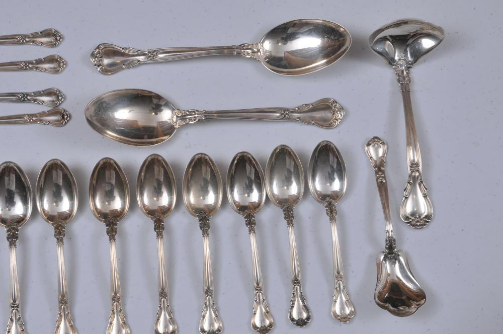 "Lot 100: Gorham ""Chantilly"" pattern sterling silver 61 piece partial flatware set. Includes"" (8) forks- 7"". ( 8) cream soup spoons- 6-1/4"". (7) salad forks- 6-1/2"". (8) solid butter knives- 6"". ( 8) ice tea spoons- 7-3/4"". (16) teaspoons- 5-7/8"". (2) large se"