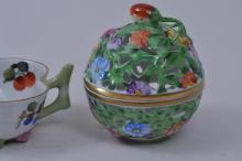 "Lot 106: Two pieces of Herend porcelain. Small reticulated floral covered jar. Leaf shaped cup with relief branch and flower base. Cup- 4-1/4"" wide."
