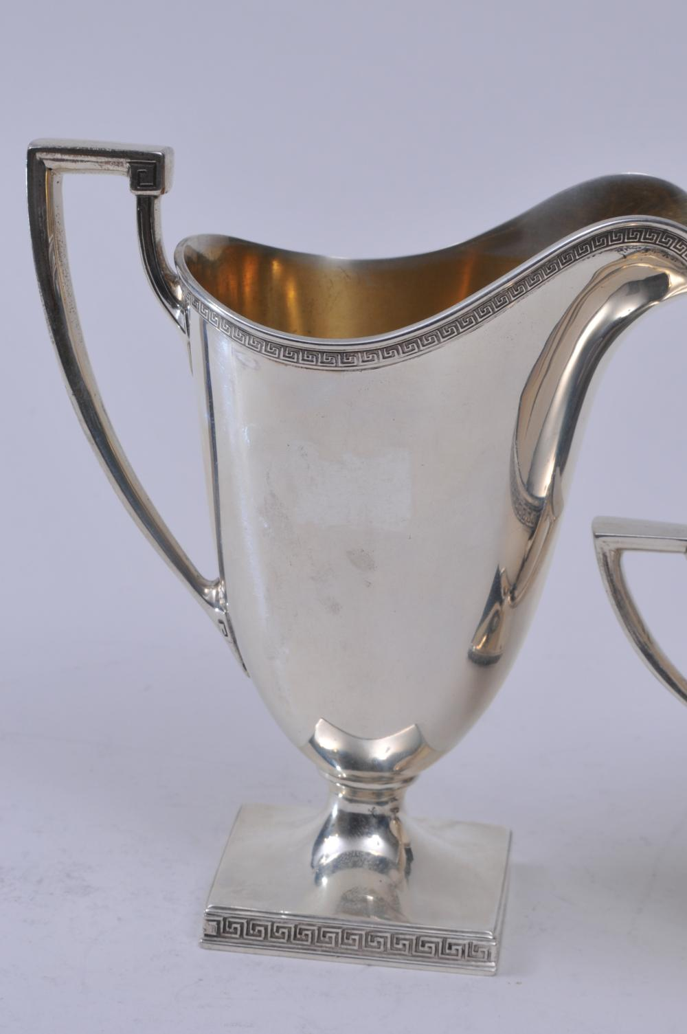 """Lot 105: Gorham sterling silver sugar and creamer. Classical form with Greek Key borders. Gilt interior on creamer. Creamer- 5-3/4"""" high. 14.6 ozt. Total weight. Good condition."""