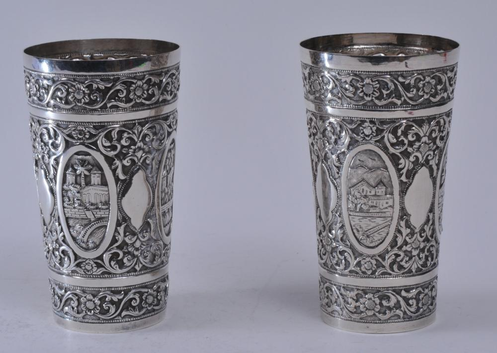 """Pair of 19th century silver repousse decorated beaker cups. Possibly Chinese Export silver. Unmarked. Oval panel landscape decorations. Flower and vines. Good condition. 5-1/8"""" high.  13.4 ozt."""