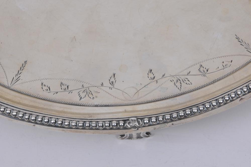 """Lot 120: Early 19th century large footed silver tray. Beaded border. Engraved vine decorated scroll feet. Hallmarked on rim. Slight dents on side rim. 13"""" diameter. 30.8 ozt."""