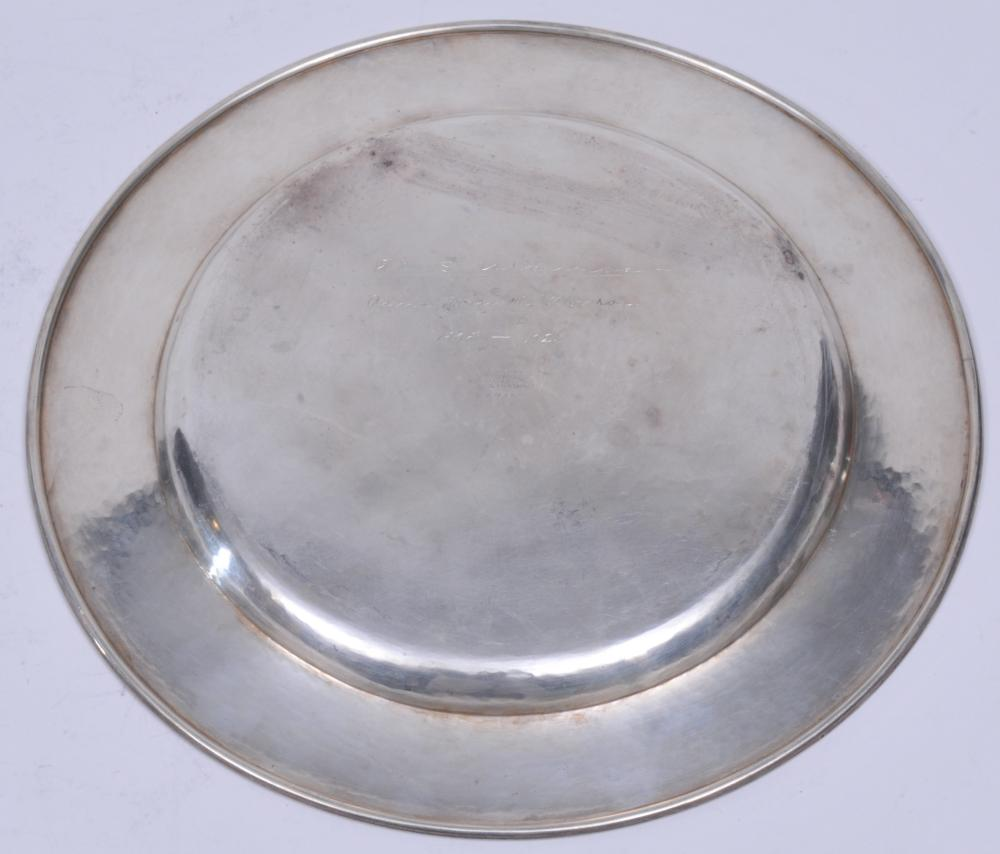 "Lot 123: Kalo sterling silver Arts and Crafts hand wrought large hand hammered round plate. 1923 inscription on base. Good condition. Light scratches. 11"" diameter. 19.2 ozt."