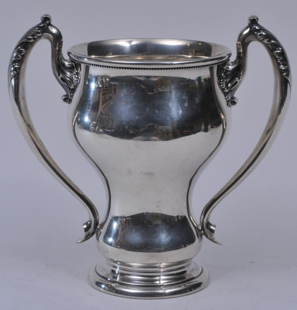 """Large sterling silver two handle trophy-Loving cup. Leaf decorated handles. 1/8"""" small ding on body. Good condition. Beaded border under rim. 9-3/4"""" high.  31 ozt."""