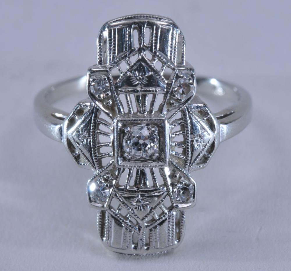 Lot 157: 18k white gold and diamond ring. Art deco style, with elaborate detailing and trillium flower design. Center diamond is near colorless, European cut, measures approximately 3.0mm in diameter. Four accent diamonds are round single-cut, approximately 1