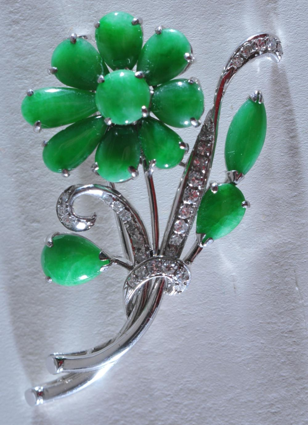 Lot 152: 14 karat white gold diamond and jadeite mounted flower form pin. Good quality and color jade stones. Approx. 27 mounted diamonds. 10.2 grams.