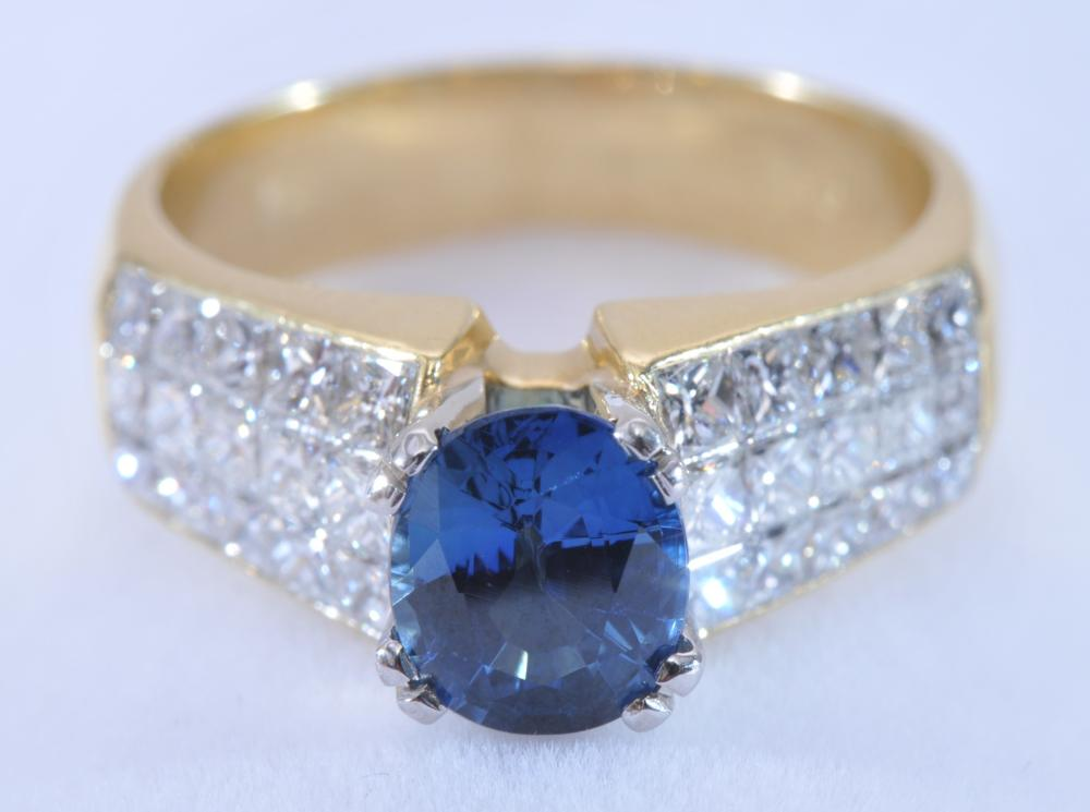 18 karat yellow gold ring, featuring a center mounted sapphire, and invisible set diamonds. Sapphire is good colour, light blue. Oval shape, measuring approximately 8 x 6.5mm. 30 invisible-set square diamonds on shoulders. Faintly marked .750. Finger
