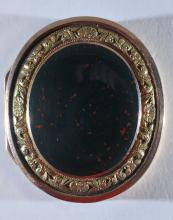 Lot 153: 14 karat gold antique Bloodstone mounted oval gold vinaigrette. Bloodstone cover with shell and leaf border. Interior with floral pierced decorated hinged lid. Blood stone mounted base. Inscribed numbers are the only markings. Tested as 14 karat gol