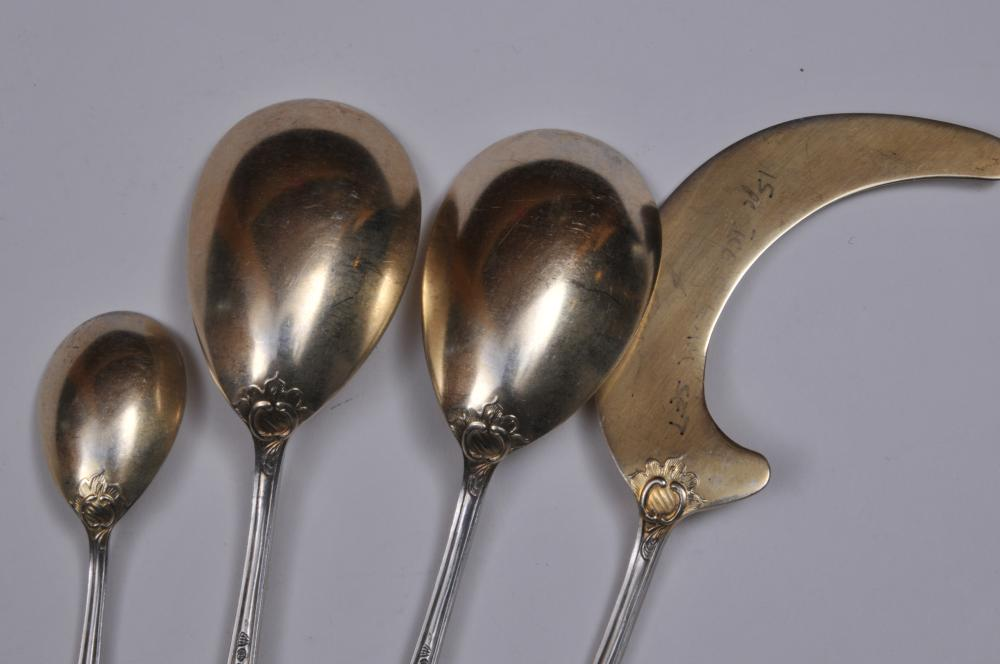 """Lot 134: .800 Continental silver Ice Cream set with asapargus tongs. 16 piece set. Includes: (12) ice cream spoons with gilt bowls. 5-3/4"""". Ice cream serving piece with gilt blade. 9-3/4"""". (2) serving spoons with gilt bowls. 8-1/2"""". Asparagus tong with gilt b"""
