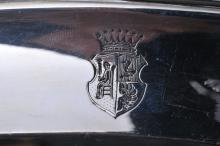 """Lot 182: Possibly French sterling silver oval paneled tray with relief garland and leaf decorated border. Heraldic crest. Hallmarked on back rim. Good condition. 16-3/4"""" x 11"""". 35.2 ozt."""