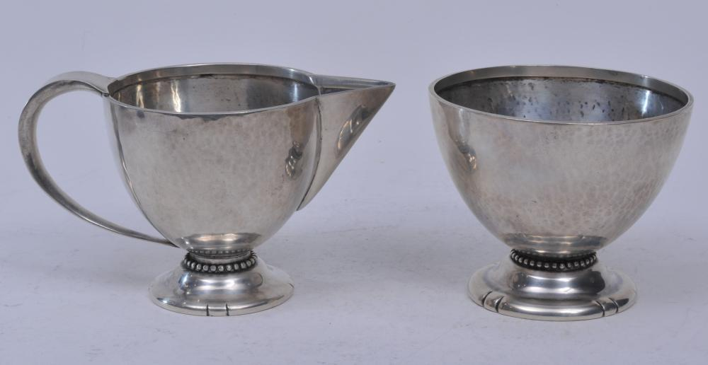 "Lot 183: DeMatteo hand hammered Arts and Crafts style sterling silver creamer and sugar. Hand hammered surface. Beaded borders and edge cut design on bases. Creamer- 3-1/4"" high. Sugar- 4"" diameter. 11.9 ozt. Good condition."
