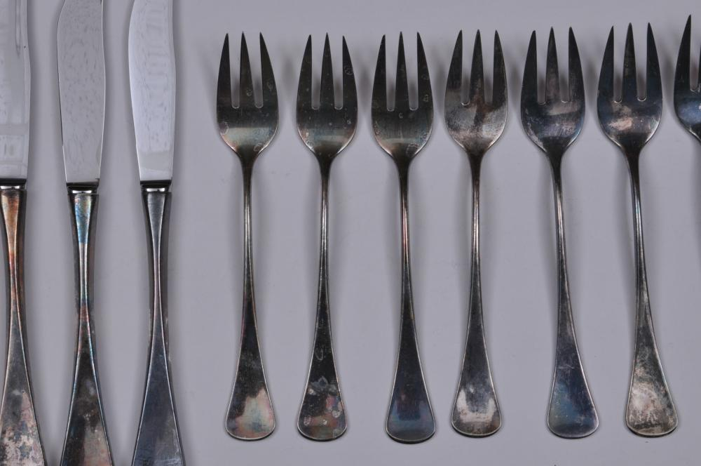 "Lot 135: W & S Sorensen. Denmark. Sterling silver. Mid Century Modern design 28 piece partial flatware set. Includes: (9) forks- 7-3/4"". (9) forks- 6-3/4"". (9) knives- 8-3/4"". (1) large solid silver serving spoon- 8-1/4"". Nine knife handles at 1.0 ozt each. T"