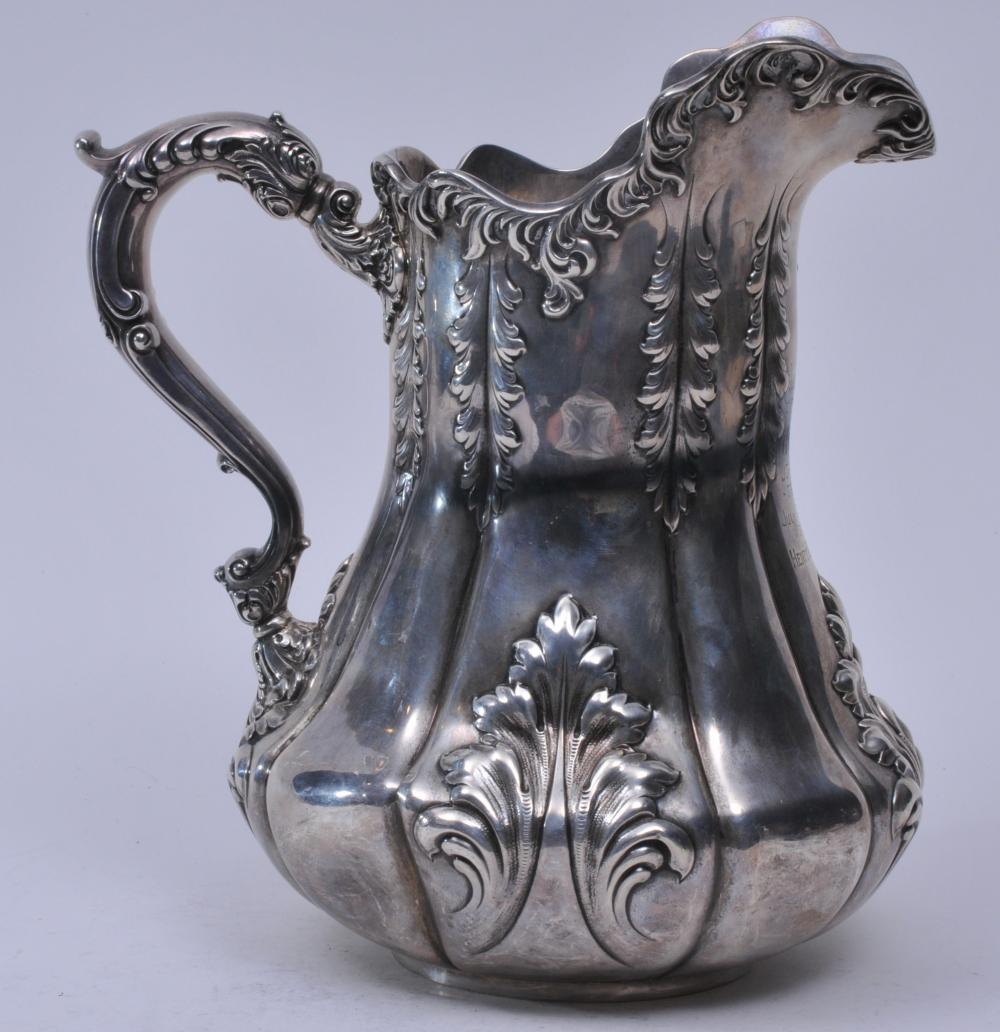 """Lot 167: Dominick & Haff large sterling silver ornate water pitcher. Lobed body with elongated relief acanthus leaf decoration. Leaf scrolled handle. Presentation inscription on front- """"Ardsley Club Golf Johnson Trophy. July 4, 1904. Won by Henry B. Galey"""". 1"""