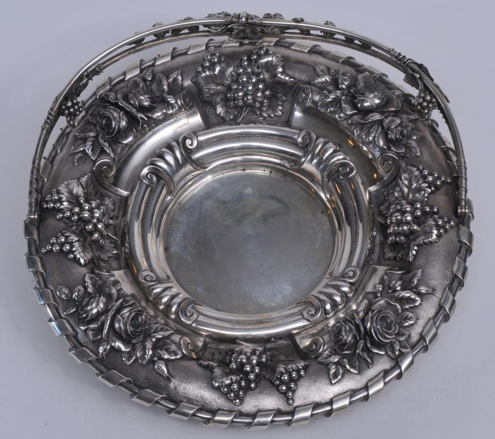 """Large ornate heavy high relief floral repousse handled basket. Floral and grape decorated handle. Large floral and grape leaf decorated body. Possibly Portuguese. Hallmarked. 13-1/2"""" diameter.  47.1 ozt.  Good condition."""