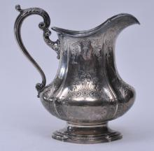 "Lot 168: ??? Makers. Large sterling silver water pitcher. Paneled body with chased floral garland and leaf decoration. 10-1/2"" high. 33.8 ozt."