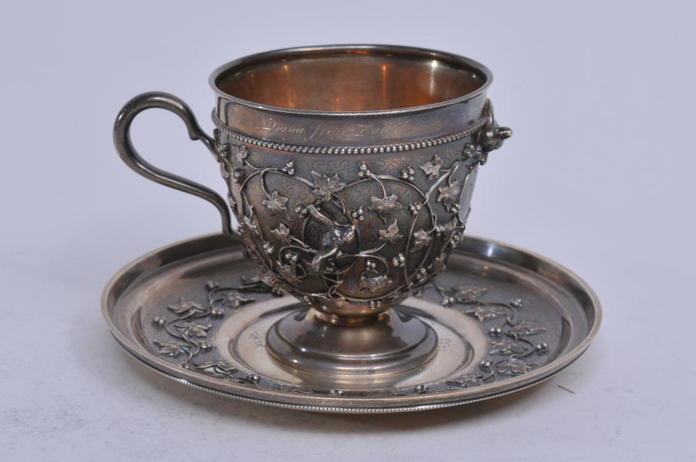 """Tiffany & Co. makers sterling silver """"Holly"""" pattern Victorian 1870 cup and saucer with high relief applied vine and bird decoration. Inscription on saucer. Monogram on cup. Cup with 1.4"""" interior dent behind bird. Gilt interior. Cup with repair at b"""