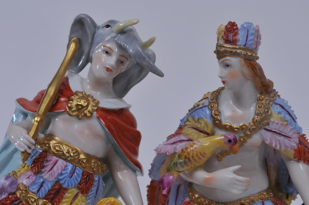 """Lot 144: Four Sitzendorf porcelain figures depicting the four continents. Elaborately dressed figures. Three with the same mark, one with a different mark. The figure holding a parrot has damage at the end of the brown bow. Tallest- 6-1/2"""" high."""