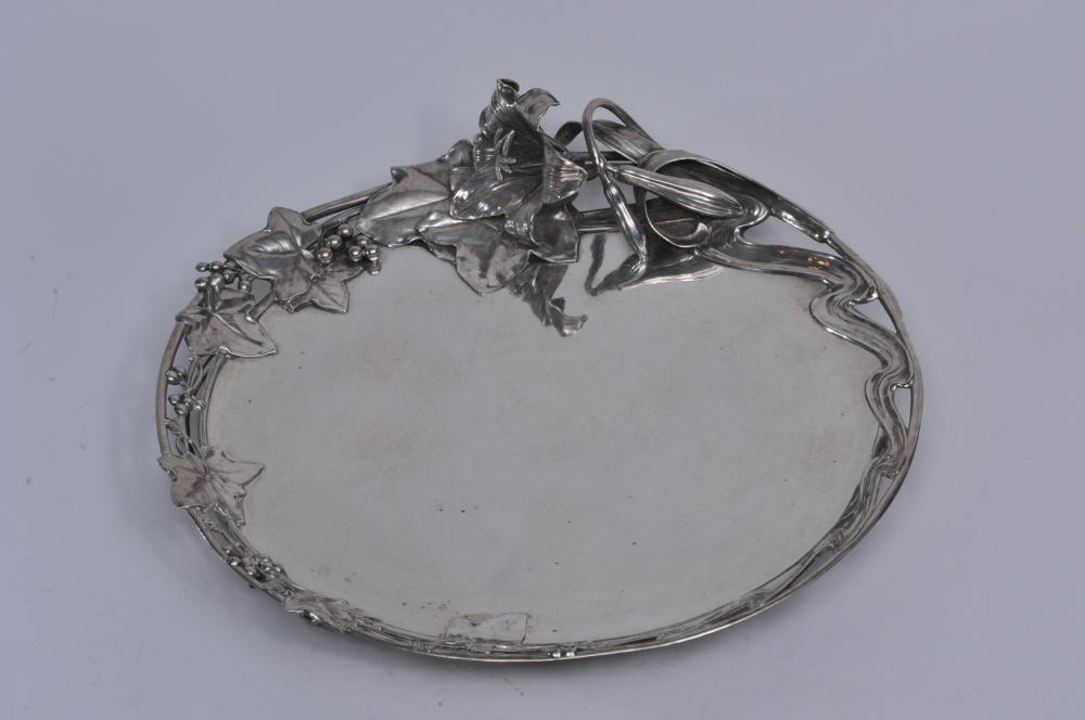 """E. Schurmann & Co. Frankfurt, Germany. .800 silver large Art Nouveau ornate round footed tray with life size relief lily flower, pods and leaves. Large grape and leafs. Pierced border. Branch form feet. 17"""" diameter.  32.3 ozt. Good condition."""