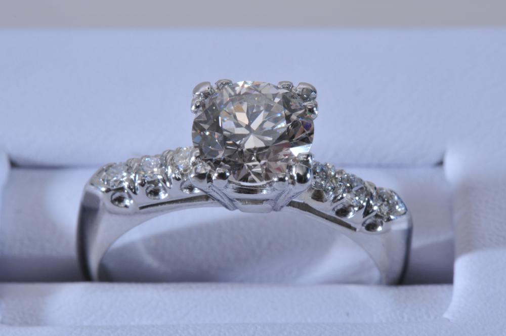 Platinum and diamond engagement ring. Center diamond is round brilliant, approximately 1.4 carats, measuring 7mm. Six round brillaint diamonds on the shoulders, approximately 2.5mm each. All stones are near colorless, nice quality. Finger size 6.5. T