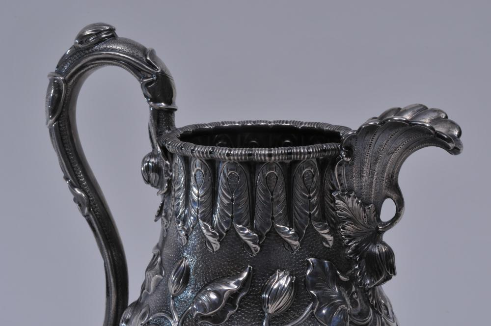 """Lot 140: Early Tiffany & Co. Grosjean & Woodard silver pitcher Coin or Sterling Silver with allover raised floral and vine decoration. Leaf form spout. Leaf decorated handle. Leaf decorated rim. Inscribed on body and base. Stippled ground. Unmarked. 10"""" high"""