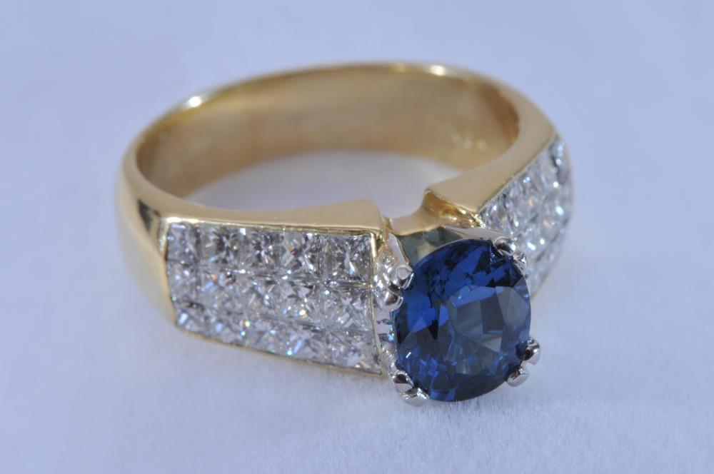 Lot 154: 18 karat yellow gold ring, featuring a center mounted sapphire, and invisible set diamonds. Sapphire is good colour, light blue. Oval shape, measuring approximately 8 x 6.5mm. 30 invisible-set square diamonds on shoulders. Faintly marked .750. Finger
