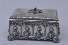 "Lot 173: 19th century Continental silver Gothic decorated rectangular covered box. Gothic panels with raised leaf decoration. Leaf form feet. Cut out Gothic base. Engraved decoration. Unmarked. 6-1/2"" wide. 3-3/4"" high."