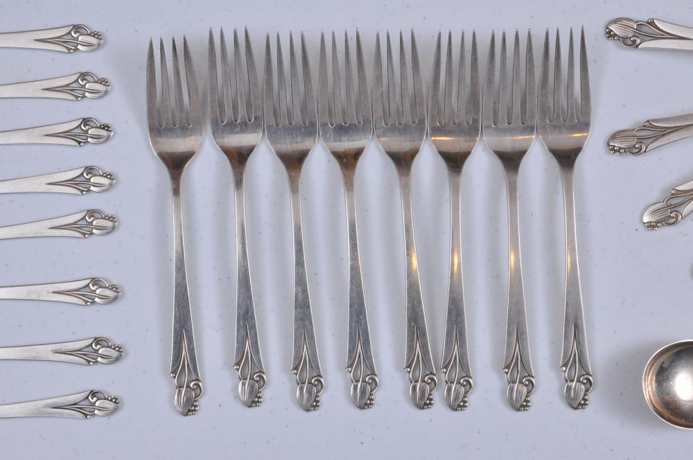 "Lot 198: Frank W. Smith Co. Makers. Sterling silver ""Wood Lily"" pattern. 61 piece flatware set. Includes (12) cream soup spoons- 6-1/2"" (8) forks- 7-1/2"" (8) salad forks- 6-3/4"" (11) teaspoons- 6-1/2"" (8) solid butter knives- 6-1/4"" (6) lunch knives- 8-3/4"""