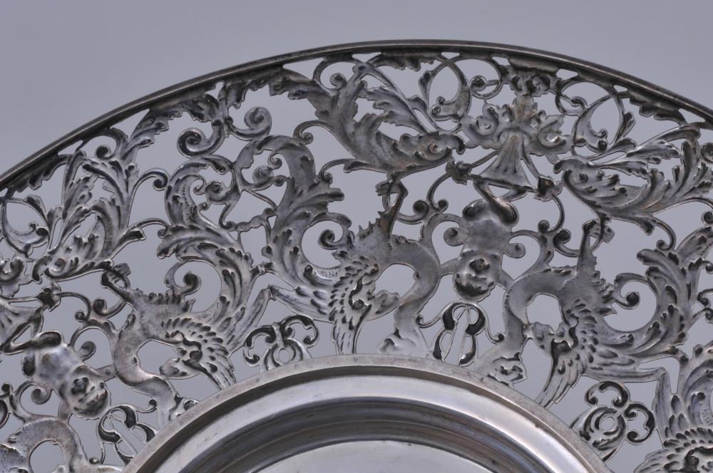 "Lot 186: Ornate sterling silver pierced round tray with cherub, griffin and dolphin figural decoration. RW makers mark. 11"" diameter. 16.6 ozt."