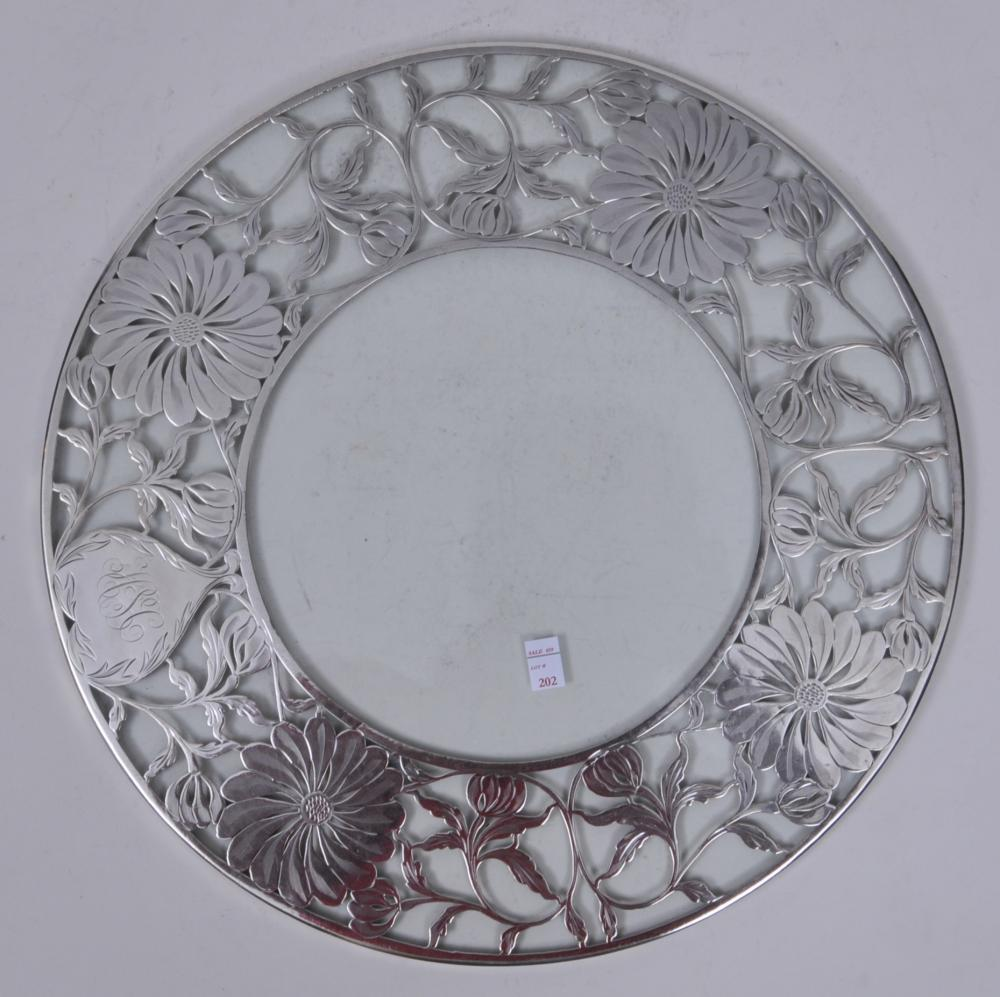 "Lot 202: Large sterling silver overlay glass dish. Heavy etched floral sterling pattern. Monogrammed. Faintly marked on sterling on one side rim. Slight scratches to glass. 14"" diameter. 1/4"" deep."