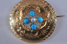 Lot 206: 18k yellow gold antique brooch, featuring four round turquoise beads, and a cultured pearl. Round design, featuring engraved floral décor. Brooch measures 29mm in diameter, total weight of 4.5g. Small dents and bends are present.