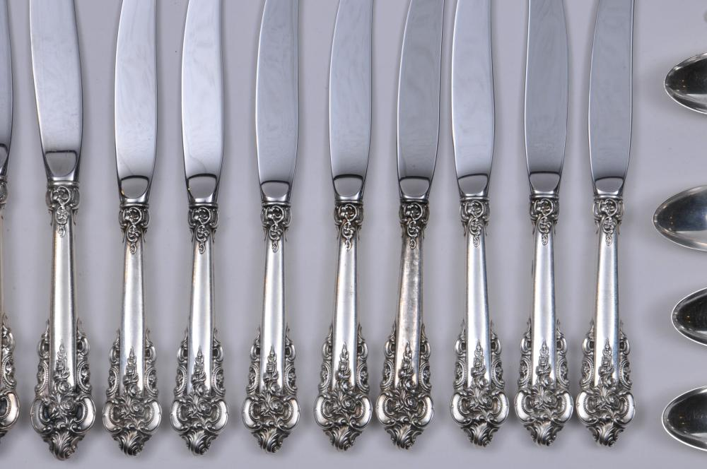 "Lot 205: Wallace ""Grand Baroque"" sterling silver 60 piece partial flatware set. Includes: (8) large forks- 8""(8) large knives- 9-3/4"". (8) knives- 8-7/8"". (8) forks- 6-1/2"". (12) teaspoons- 6-1/4"". (8) cream soup spoons- 6-1/4"". (8) handled butter knives- 6-1"