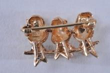 Lot 207: 10k yellow gold brooch, featuring three birds. Three round gemstones, one ruby, one pink sapphire, and one blue sapphire. Stones approximately 2.5mm each. Overall size of brooch is 12.5 x 22mm. Hallmarked 10k. Total weight of 3.2g.