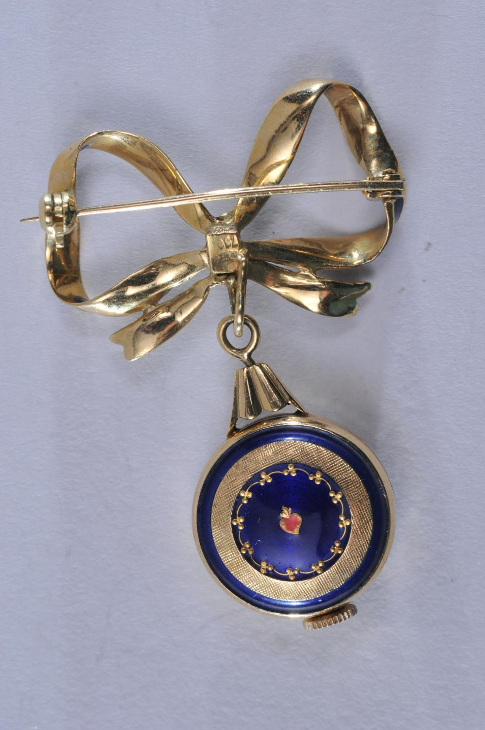 Lot 214: 18k yellow gold watch brooch. Blue bow design, featuring blue enamel accenting. Semag 17 jewel mechanical watch, runs and stops, but in overall nice condition with a crisp dial and gold hands and markers. Hallmarked 18k. Overall size of brooch is 45