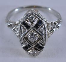 Lot 216: 18k white gold art-deco style diamond ring. Elaborate milgrain and detailing, with engraved décor. Center diamond is a round brilliant, near colorless, approximately 3.0mm in diameter. Two small single-cut diamonds on each end of the ring, approximat