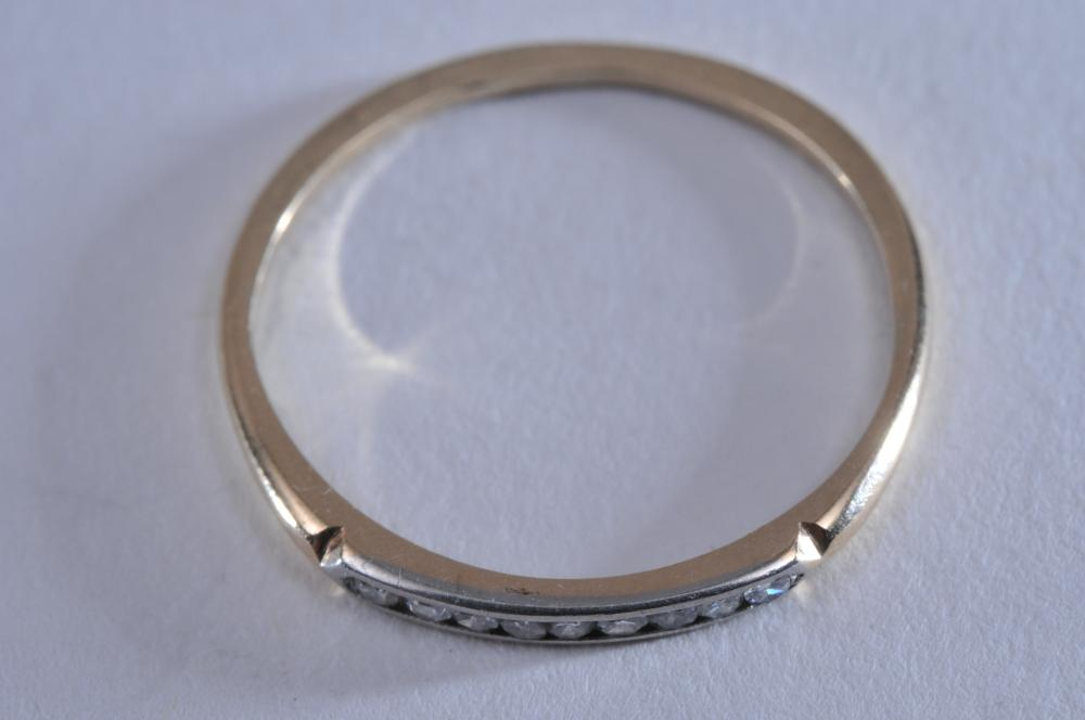 Lot 219: 14k yellow gold and platinum diamond band ring. Contains 9 channel-set round brilliant diamonds, approximately .01ct each. Band is 1.8mm in width, finger size 7.25. No hallmarks. Total weight of 1g.