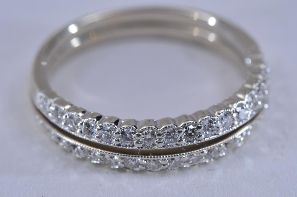 Lot 215: 14k white gold and diamond band ring. Double-band style with single shank, top width of 4.5mm, with 34 prong-set round brilliant diamonds. Near colorless, approximately 1.3mm each. Finger size 6. Hallmarked 14k. Total weight of 2.7g.