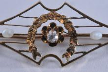 Lot 220: 14k yellow gold, diamond, and pearl brooch. Diamond is a European cut, approximately 2.3mm in diameter. Two baroque pearls. Overall dimensions of brooch is 36 x 14mm. Total weight of 1.2g. No hallmarks. Some wear, bending, and a broken crosswire is p